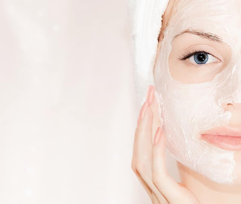 Woman with Hair in Towel Using Face Mask