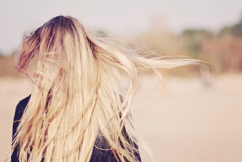 Back View of Woman with Long Blond Hair Blowing in the Wind