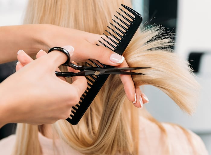 Woman With Blond Hair Getting a Trim with Scissors and Comb